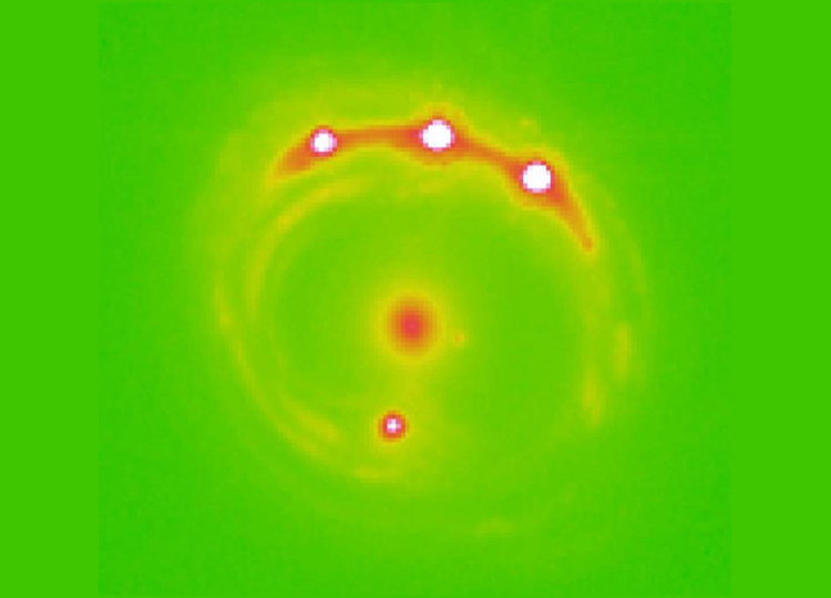 Изображение на квазара RXJ1131-1231, подсилен с гравитационна леща. Червеното петно в центъра на галактиката действа като леща, а четирите светли петна (три отгоре и едно отдолу) са увеличени изображения на един и същи квазар. Смята се, че има трилиони планети в центъра на елиптичната галактика на това изображение. Сн: Ohio State University
