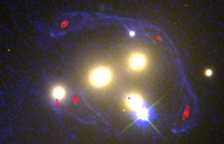Наблюденията на обсерваторията Atacama Large Millimeter Array разкриха, че тъмната материя (очертана в червени контурни линии) се придържа към звезди в тази галактическа катастрофа.