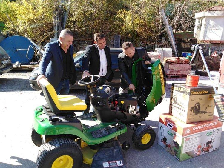 Николай показва на кмета и служителите новата техника за косене
