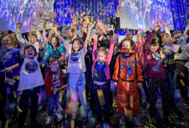 Главният изследовател на New Horizons Алън Стърн (в центъра) празнува с ученици в момента, в който е планиран космическият кораб да достигне най-близкия си подход до обекта на Пояса на Кайпер Ултима Туле на 1 януари 2019 г. в Лабораторията по приложна физика на Университета Джонс Хопкинс. Това е най-далечният полет в историята.