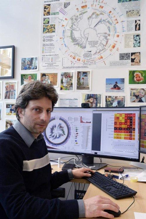 Никола Сегата в лабораторията си в Cibio University в Тренто. Човешкият микробиом, представена като дървото на живота зад него