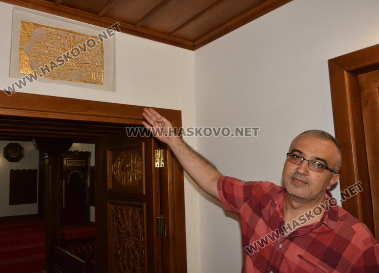 Иса Агушев показва надписът с годината на построяване на джамията